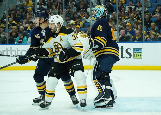 Boston Bruins center Patrice Bergeron screens Buffalo Sabres' Carter Hutton and Rasmus Ristolainen from a potential shot