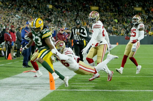 Former San Francisco 49ers linebacker Reuben Foster tackling Green Bay Packers running back Aaron Jones out of bounds