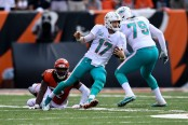 Miami Dolphins quarterback Ryan Tannehill slips away from a Cincinnati Bengals tackle by Preston Brown