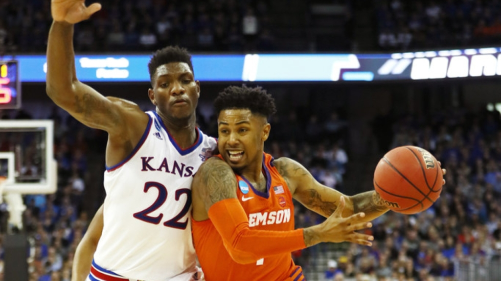 Clemson Tigers player Shelton Mitchell drives to the basket while being defended by Kansas Jayhawks defender Silvio De Sousa during the second half in the 2018 NCAA Men's Basketball Tournament Midwest Regional