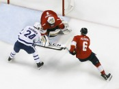 Former Florida Panthers defenseman Alex Petrovic assists goaltender Robert Luongo to defend the net against the Toronto Maple Leafs