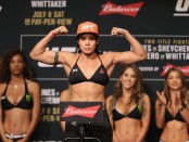 MMA fighter Amanda Nunes poses on the scale at UFC weigh-ins before UFC 213