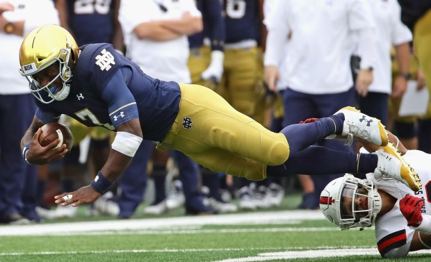 Notre Dame Fighting Irish quarterback Brandon Wimbush is tripped by Brandon Martin against the Ball State Cardinals