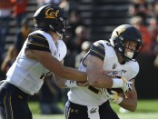 California Golden Bears quarterback Chase Garbers hands the ball off to teammate Patrick Laird against the Oregon State Beavers