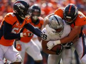 Oakland Raiders running back Doug Martin is being tackled against the Denver Broncos