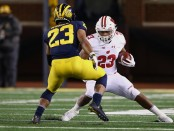 Wisconsin Badgers running back Jonathan Taylor tries to get around a potential tackle against the Michigan Wolverines