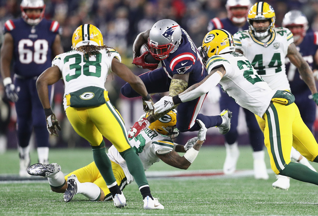 Former New England Patriots wide receiver Josh Gordon is tackled by Green Bay Packers Jaire Alexander and Josh Jones after making a reception
