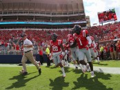 Former Ole Miss Rebels head coach Hugh Freeze running onto the field against the Wofford Terriers