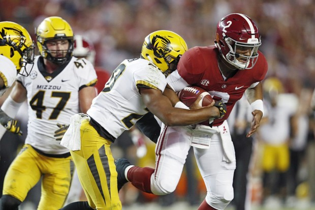 Alabama Crimson Tide quarterback Jalen Hurts is tackled by Khalil Oliver after catching a pass against the Missouri Tigers