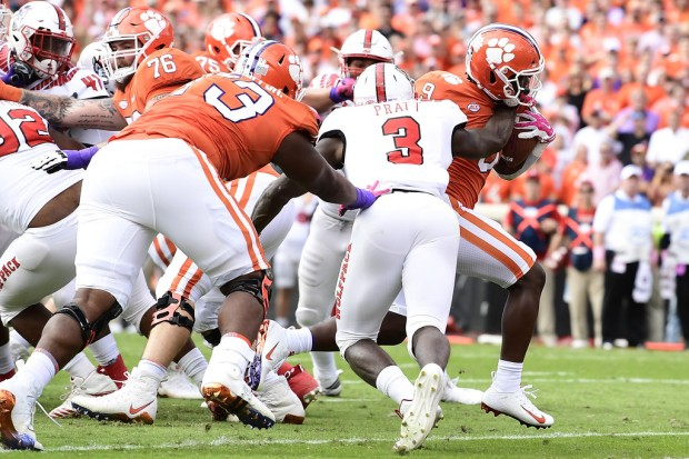 Clemson Tigers running back Travis Etienne running the ball against the North Carolina State Wolfpack
