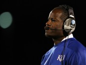 Former Kansas Jayhawks head coach Turner Gill watches from the sidelines against the Oklahoma Sooners