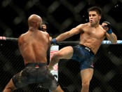 MMA fighter Henry Cejudo kicks Demetrious Johnson at UFC 227 in the second round of the UFC Flyweight Title Bout