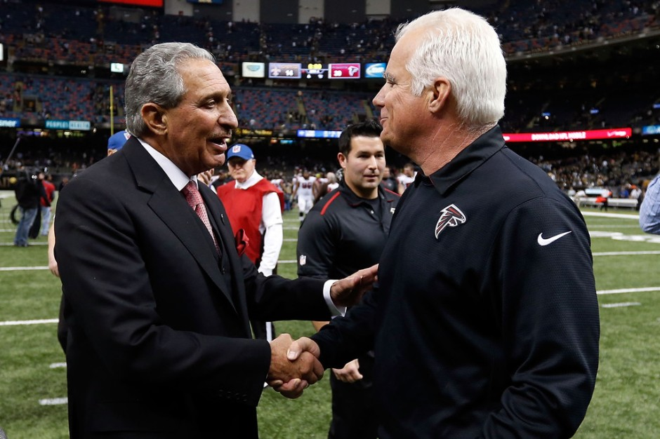Former Atlanta Falcons head coach Mike Smith shaking hands with Arthur Blank