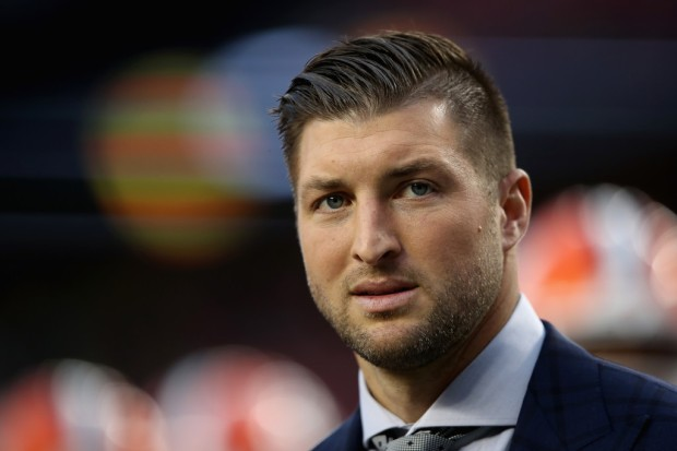 Former NFL player and College Football legend Tim Tebow looks on during warm-ups before the CFP National Championship between the Alabama Crimson Tide and the Clemson Tigers