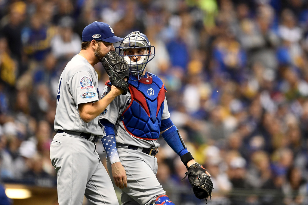 Former Los Angeles Dodgers catcher Yasmani Grandal talks to Rich Hill against the Milwaukee Brewers in the 2018 MLB playoffs
