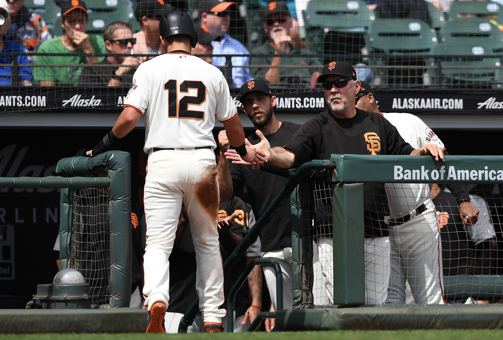 San Francisco Giants manager Bruce Bochy congratulates Joe Panik after he scores against the Atlanta Braves