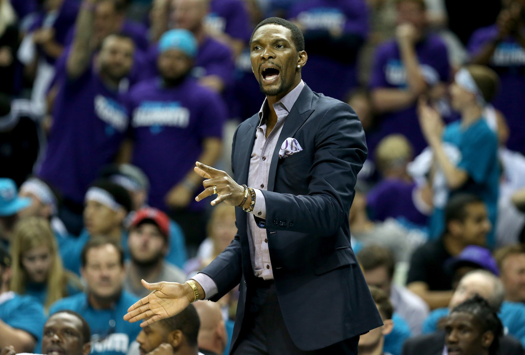Former NBA player Chris Bosh watches from the Miami Heat bench against the Charlotte Hornets during the 2016 NBA playoffs