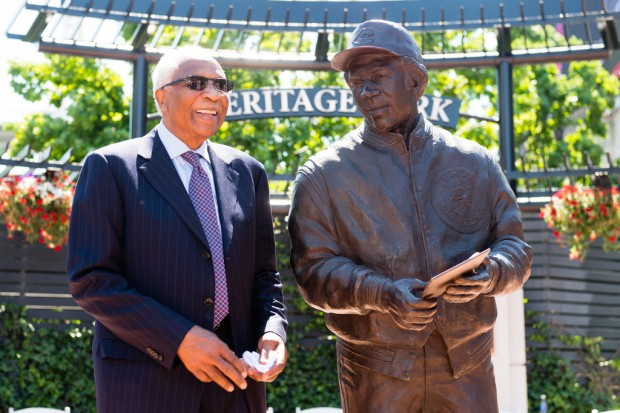 Baseball legend Frank Robinson stands with a new statue commemorating his career