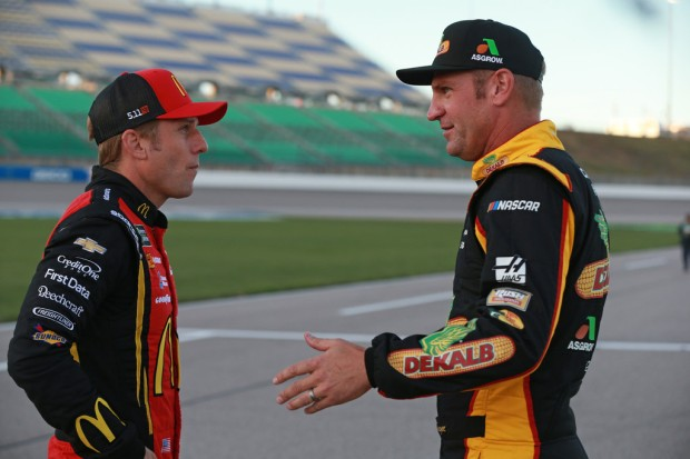 Driver Jamie McMurray talks with Clint Bowyer during qualifying for the Monster Energy NASCAR Cup Series Hollywood Casino 400 at Kansas Speedway