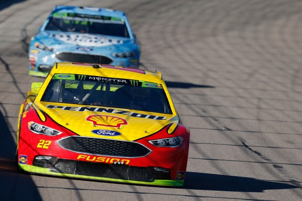Joey Logano leads Kevin Harvick at the Monster Energy NASCAR Cup Series Hollywood Casino 400 at Kansas Speedway