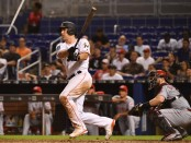Former Miami Marlins catcher J.T. Realmuto hits a double against the Cincinnati Reds
