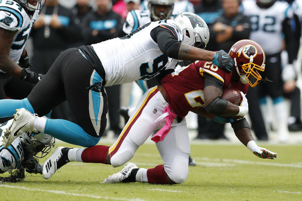 Carolina Panthers defensive end Julius Peppers tackles Adrian Peterson against the Washington Redskins