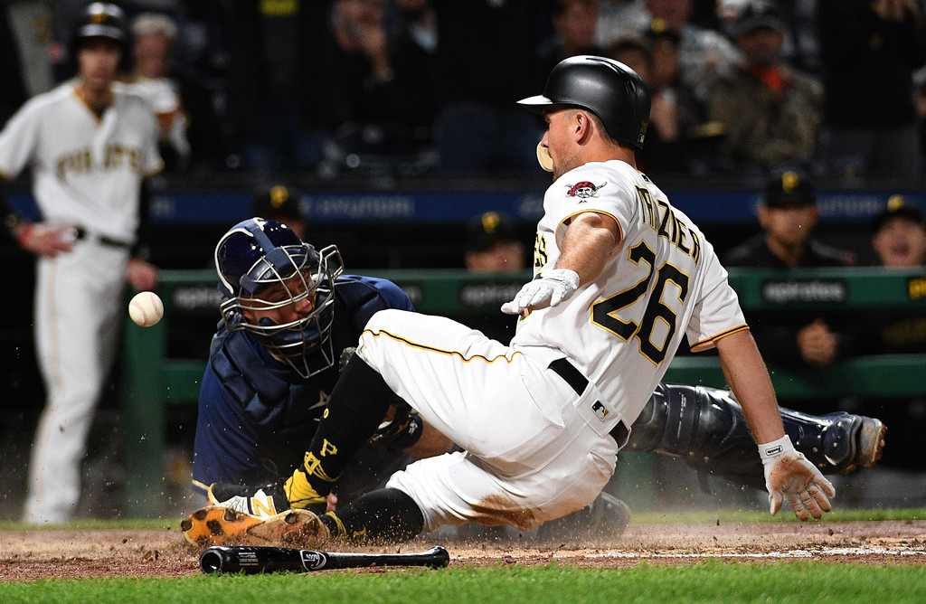 Pittsburgh Pirates second baseman Adam Frazier slides safety into home plate despite an attempted tag by Erik Kratz against the Milwaukee Brewers