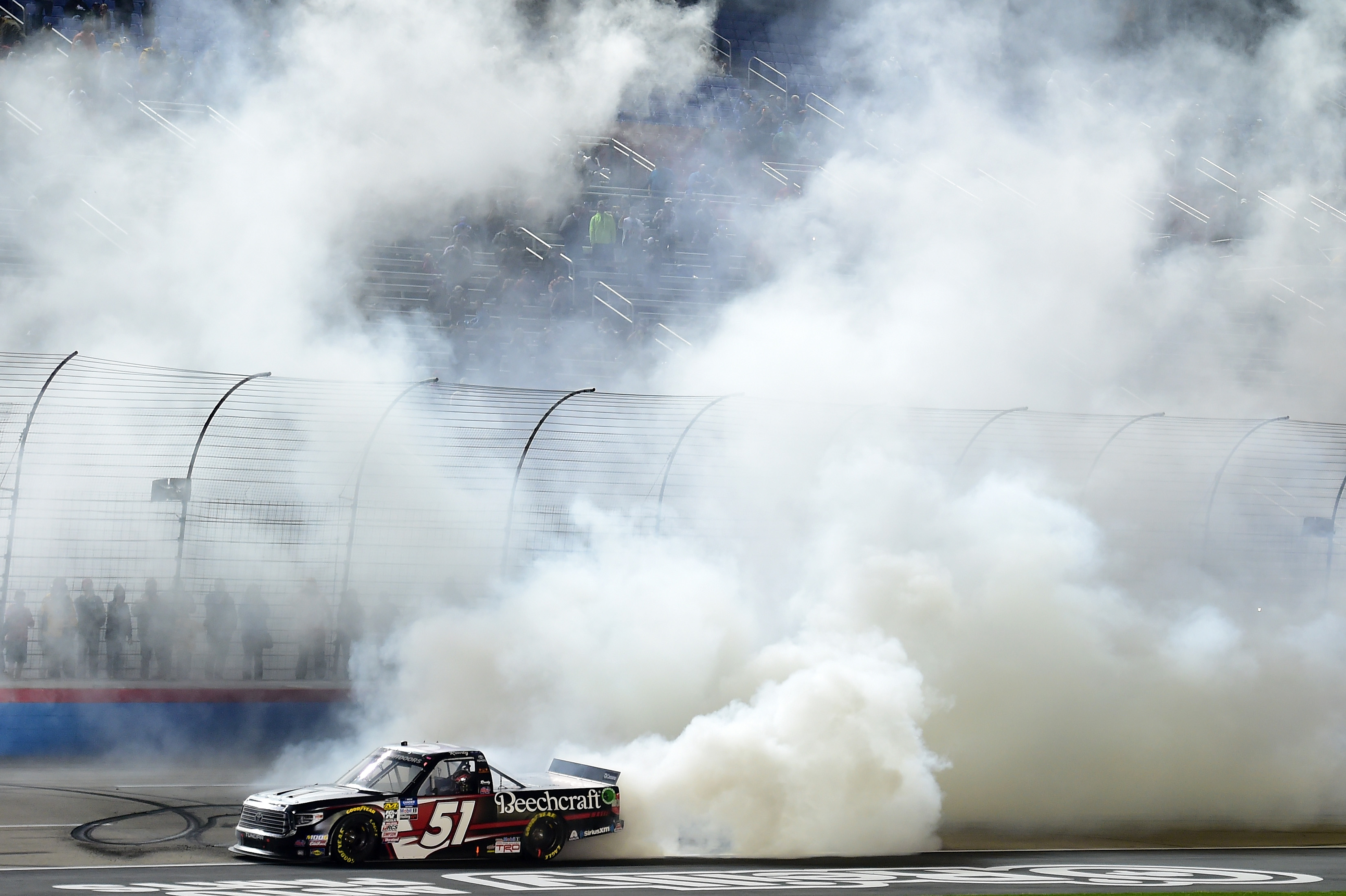 Driver Kyle Busch celebrates after winning the NASCAR Gander Outdoors Truck Series Vankor 350