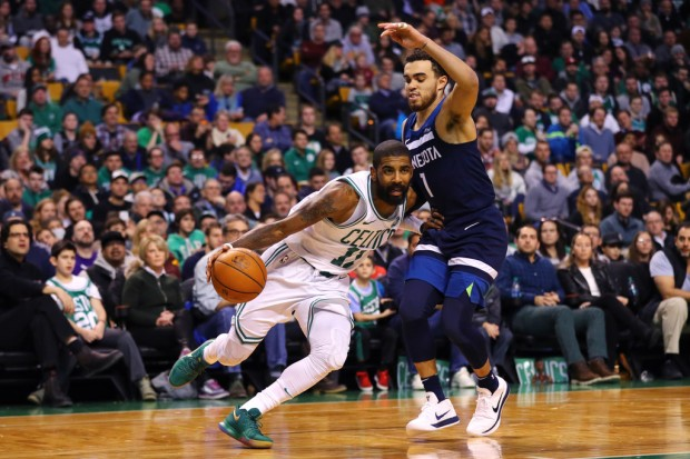 Minnesota Timberwovles guard Tyus Jones tries to defend Kyrie Irving as he drives to the basket against the Boston Celtics