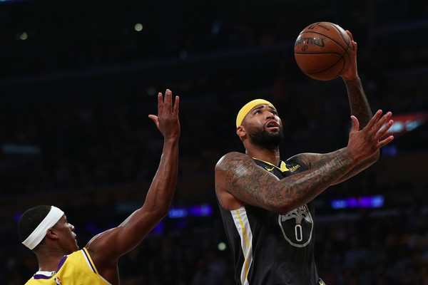 Golden State Warriors center DeMarcus Cousins drives to the basket while being defended by Rajon Rondo against the Los Angeles Lakers