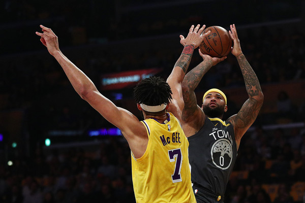 Golden State Warriors center DeMarcus Cousins shoots the ball past JaVale McGee against the Los Angeles Lakers