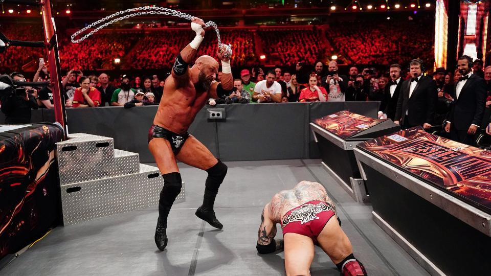 Wrestler Triple H hitting Batista with a chain outside of the ring at WrestleMania35