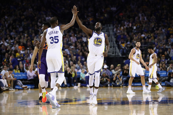 Golden State Warriors forward Kevin Durant and Draymond Green high five after a basket against the Phoenix Suns