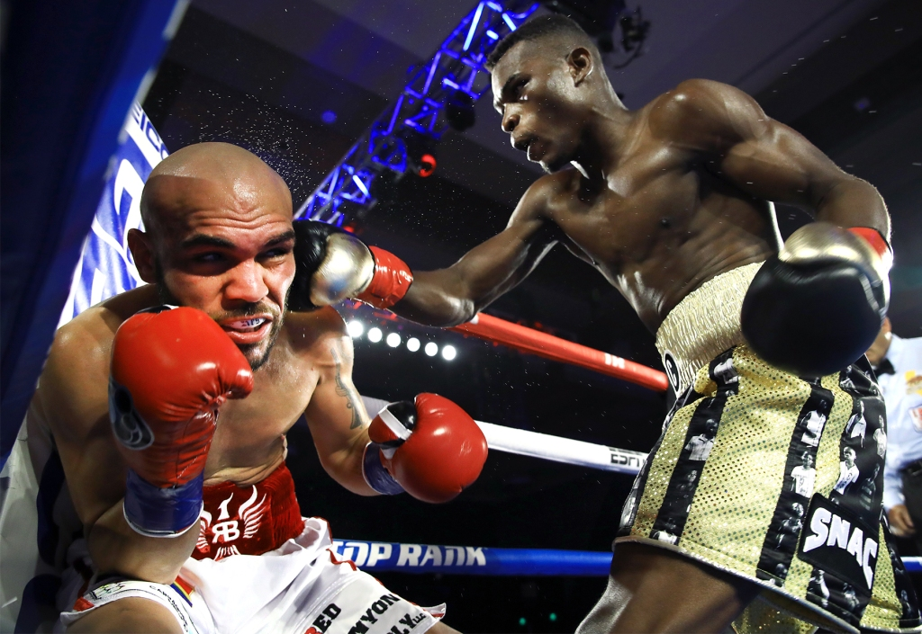 Boxer Richard Comment punches Ray Beltrán during their fight at the Pechanga Resort Casino in California