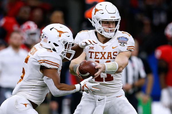 Texas Longhorns quarterback Sam Ehlinger hands the ball off to Tre Watson in the Allstate Sugar Bowl against the Georgia Bulldogs