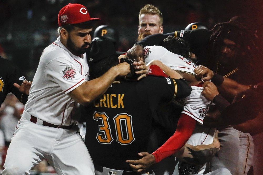 Cincinnati Reds pitcher Amir Garrett punches Pittsburgh Pirates' Kyle Crick as Garrett's teammate Eugenio Suarez attempts to break up the fight