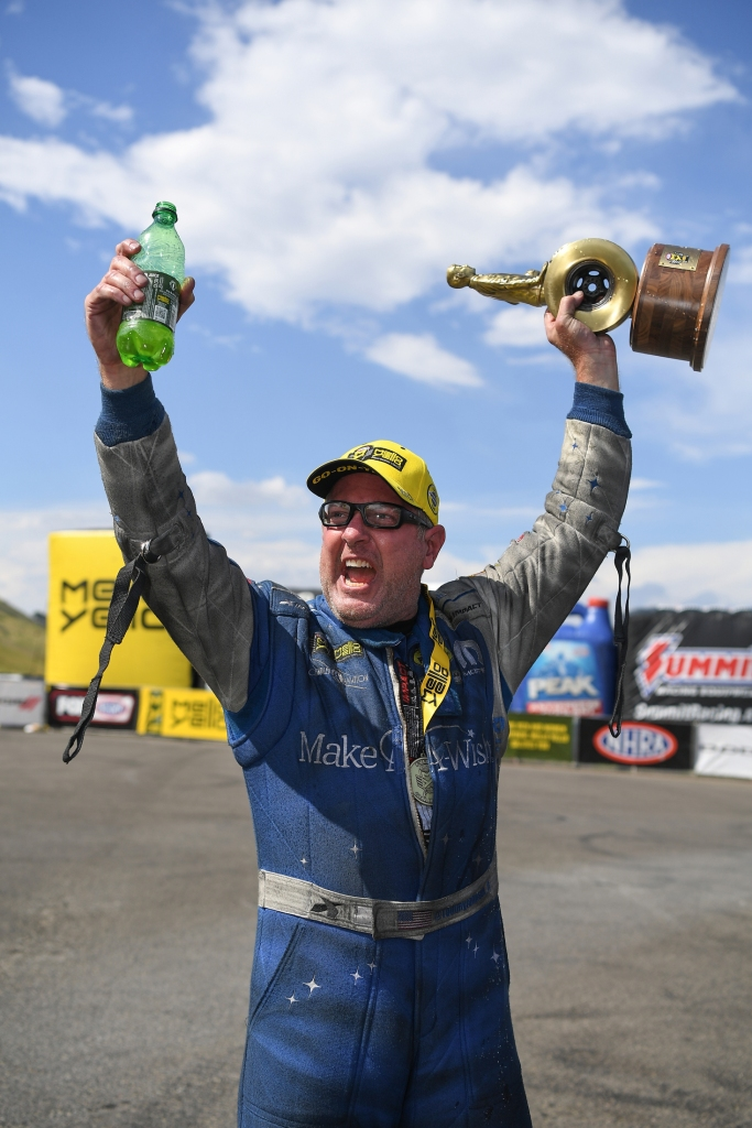 Funny Car pilot Tommy Johnson Jr. with the Wally after winning the 2019 Dodge Mile-High NHRA Nationals