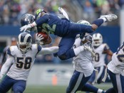 Seattle Seahawks running back Chris Carson is tackled by Cory Littleton and Michael Brockers against the Los Angeles Rams