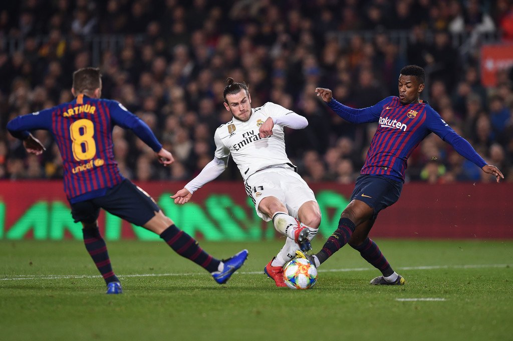Real Madrid winger Gareth Bale goes for the ball as he battles Arthur Melo and Nelso Semedo against FC Barcelona