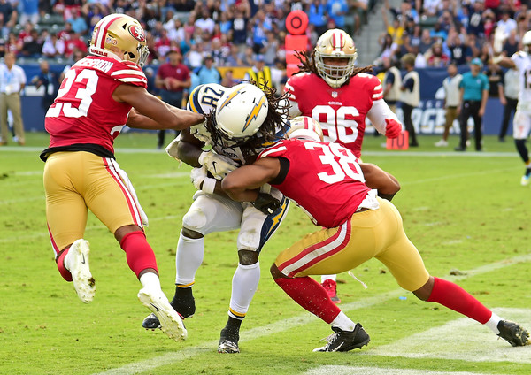 Los Angeles Chargers running back Melvin Gordon III runs the ball as Ahkello Witherspoon and Antone Exum attempt to stop him against the San Francisco 49ers