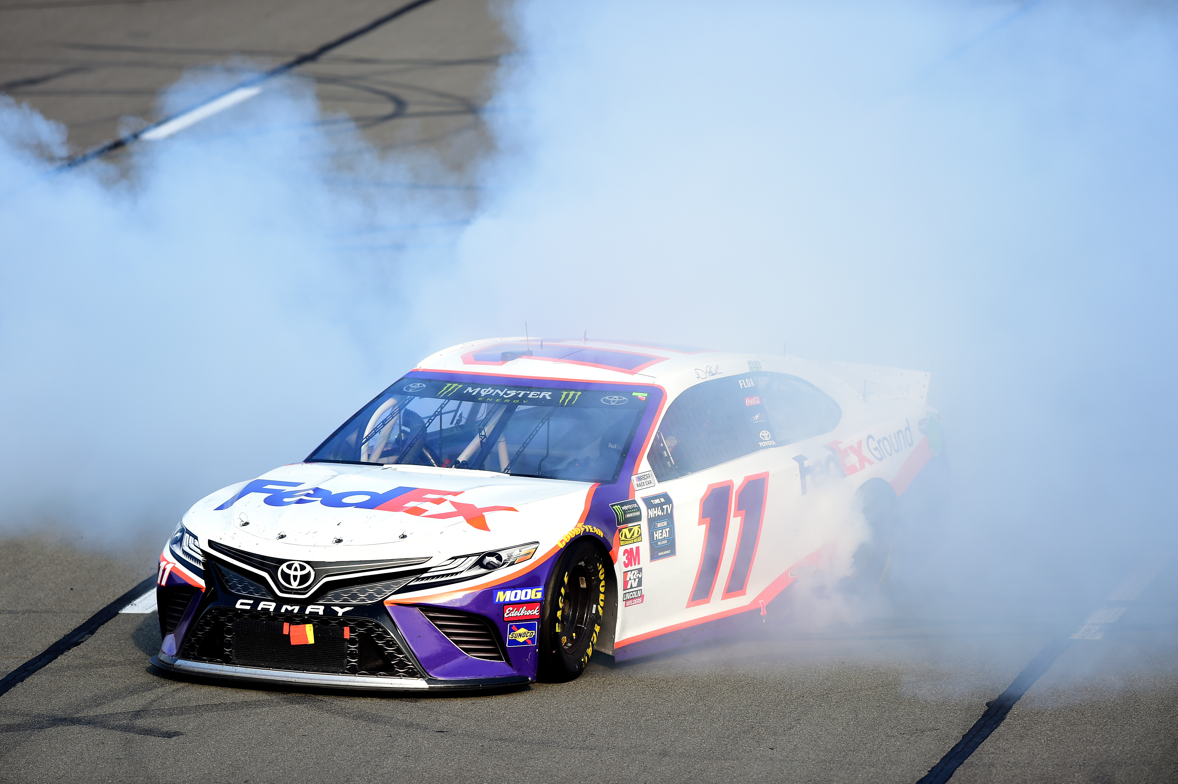 Driver Denny Hamlin celebrates with a burnout after winning the Monster Energy NASCAR Cup Series Gander RV 400