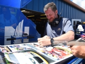 Legendary NASCAR driver and NASCAR on NBC broadcaster Dale Earnhardt Jr. signing an autograph at the Consumers Energy 400
