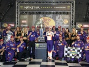 Driver Denny Hamlin celebrates with his team in Victory Lane after winning the Monster Energy NASCAR Cup Series Bass Pro Shops NRA Night Race