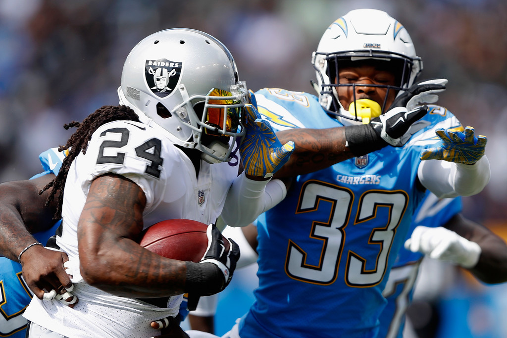 Los Angeles Chargers safety Derwin James attempts to tackle Marshawn Lynch against the Oakland Raiders