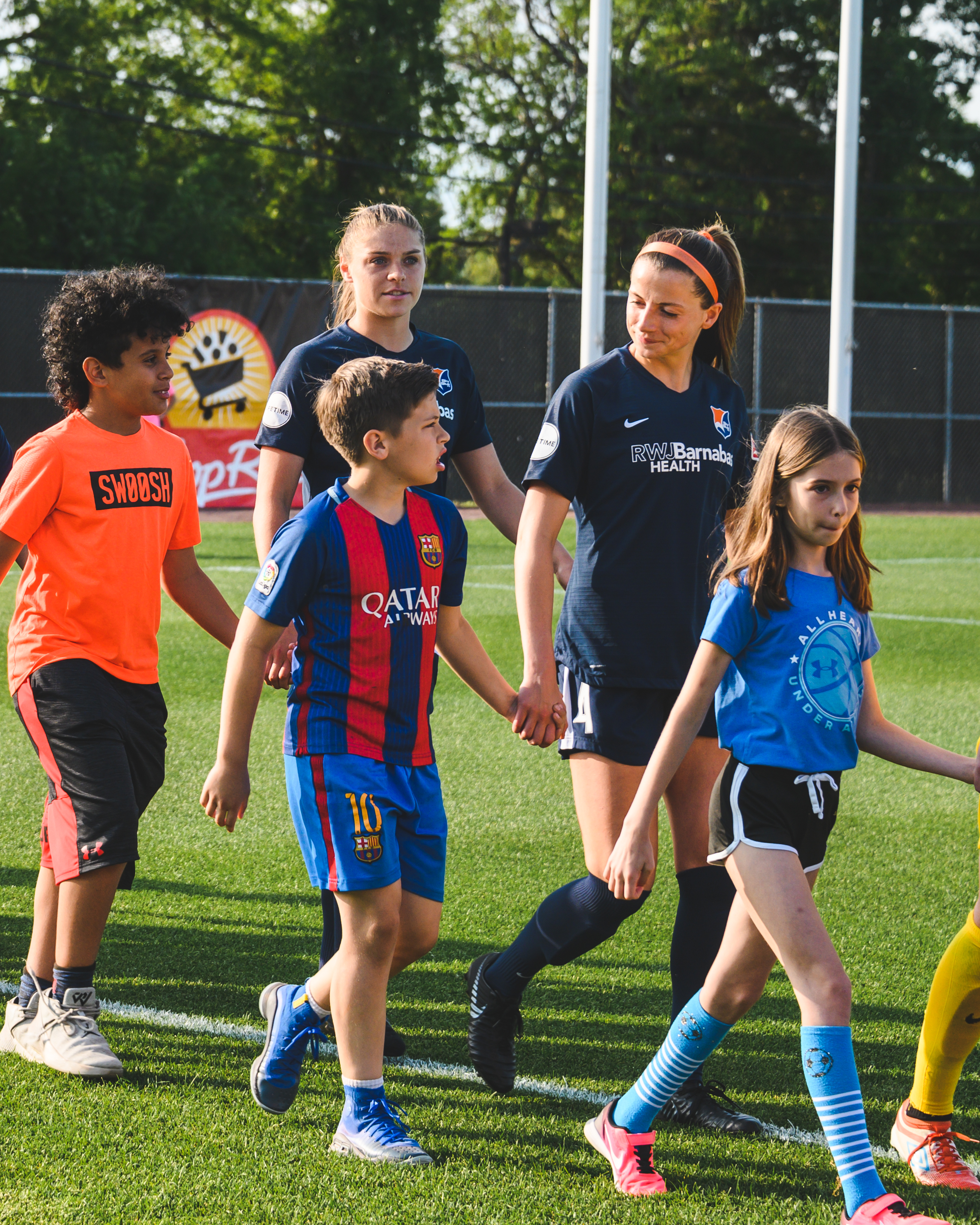 Sky Blue FC forward Paige Monaghan walking onto the field with a kid before a game