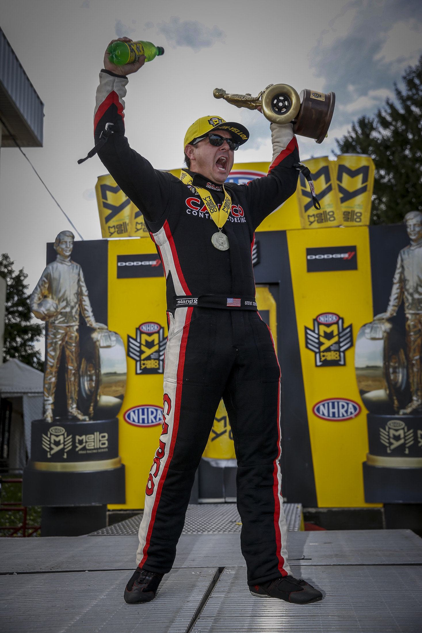 Top Fuel Dragster pilot Steve Torrence celebrating with the Wally after winning the Dodge NHRA Nationals