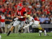 Georgia Bulldogs quarterback Jake Fromm tries to outrun Lewis Cine against the Notre Dame Fighting Irish