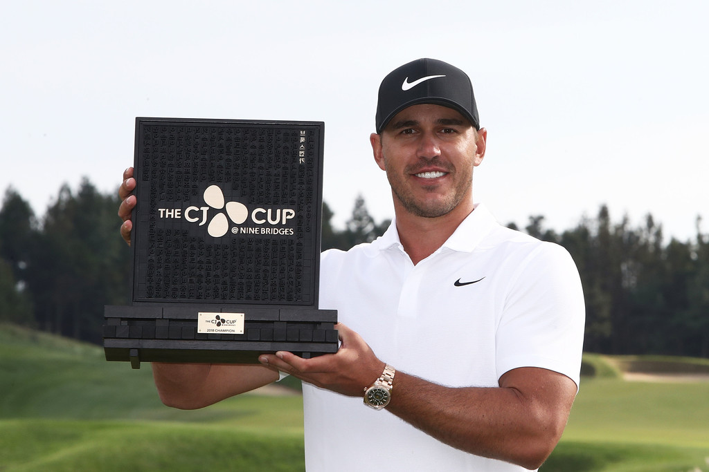 Golfer Brooks Koepka poses with the trophy after winning the CJ Cup