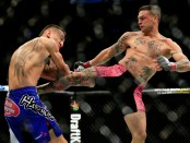 UFC fighter Cub Swanson kicks Max Holloway in their featherweight bout at the UFC Fight Night event