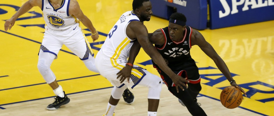Toronto Raptors forward Pascal Siakam dribbles the ball while being defended by Draymond Green against the Golden State Warriors in the 2019 NBA Finals